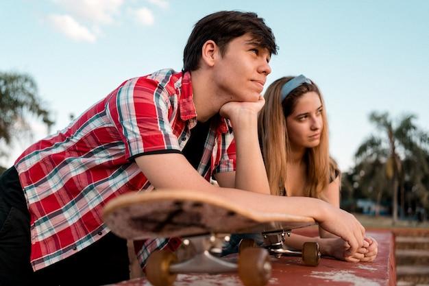 Junges paar mit skateboard, das die natur genießt