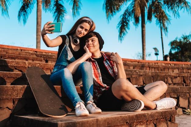 Junges paar mit skateboard, das selfie im freien nimmt