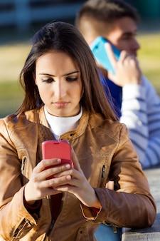 Junges paar mit smartphones im park