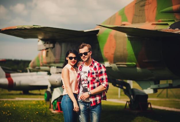 Junges paar mit sonnenbrille in der nähe des flugzeugs