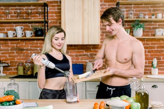 Junges paar mit stabmixer, der süßen milchshake-smoothie in der küche zu hause macht. milch nach dem training trinken. sporternährungsdiät nach dem fitnessstudio. gesunder lebensstil