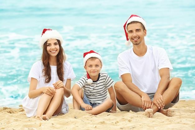Junges paar mit süßem jungen am strand. weihnachtskonzept