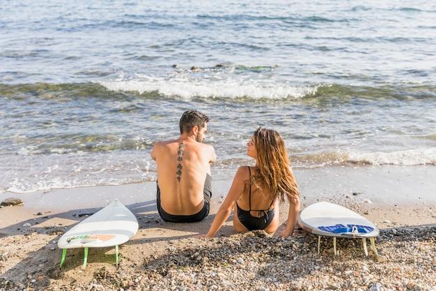 Junges paar mit surfbrettern am strand entspannen