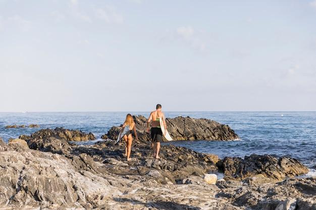 Junges paar mit surfbrettern zu fuß am ufer