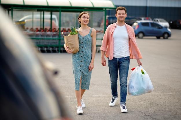 Junges paar mit taschen auf supermarktparkplatz