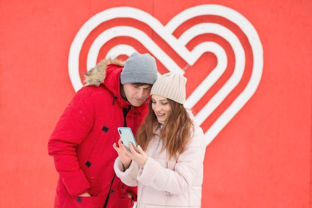 Junges paar mit telefon in der stadt nahe großem herzen an der wand. valentinstag online-shopping. hochwertiges foto