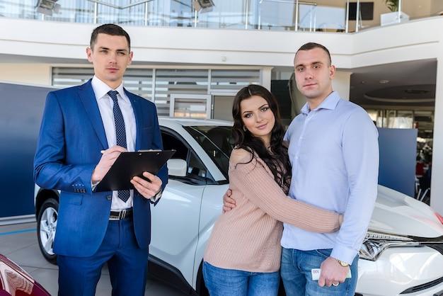 Junges paar mit verkäufer in der nähe von neuwagenunterzeichnungsvertrag