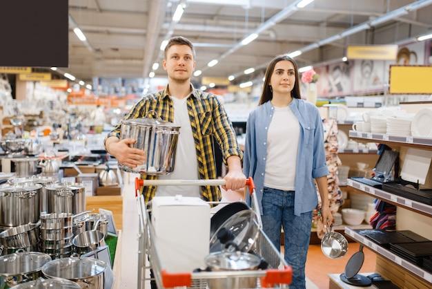 Junges paar mit wagen im haushaltswarenladen. mann und frau kaufen haushaltswaren im markt, familie im küchengeschirrversorgungsgeschäft
