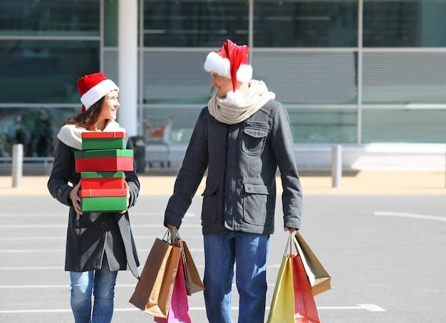 Junges paar mit weihnachtseinkäufen in der nähe eines einkaufszentrums