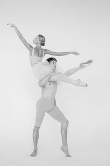 Junges paar moderne balletttänzer, die über weißem studio aufwerfen.