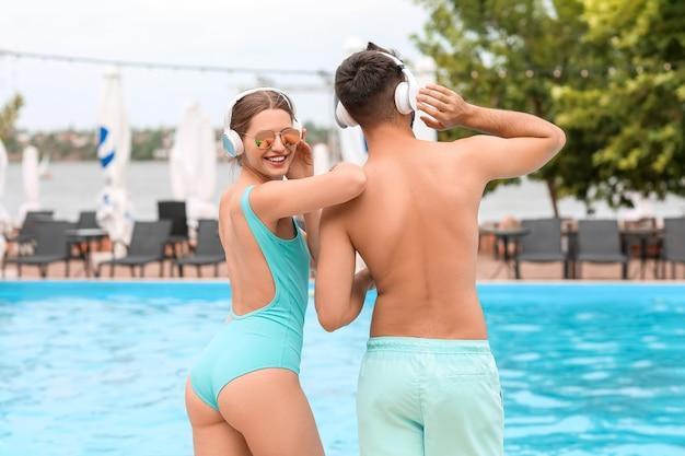 Junges paar musikhören in der nähe von schwimmbad