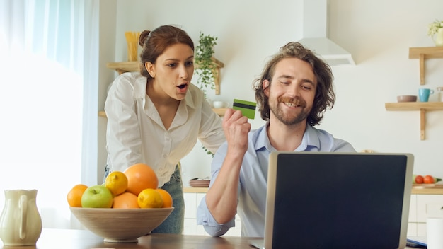 Junges paar online-shopping mit kreditkarte zahlung einkauf auf einem laptop zusammen sitzen in der hellen küche. paare, die mit spaß-ausdrucksvollem tun gewinner gestikulierende hände feiern.