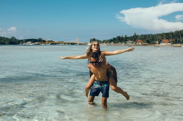 Junges paar posiert am strand, spaß im meer, lachen und lächeln