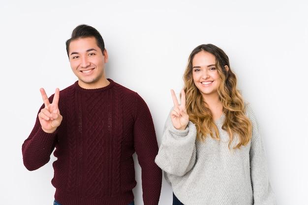 Junges paar posiert in einer weißen wand, die nummer zwei mit den fingern zeigt.