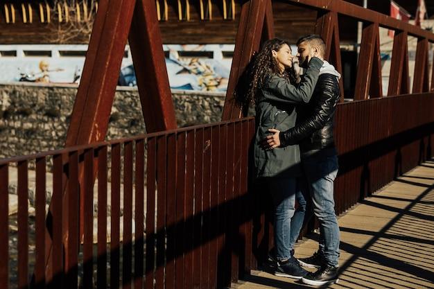 Junges paar posiert und spricht auf der alten roten metallbrücke.