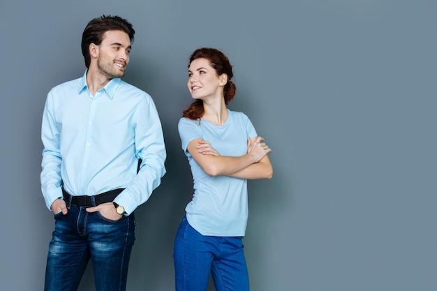 Junges paar. positive glückliche entzückte leute, die ihren kopf drehen und einander betrachten, während sie gegen grauen hintergrund stehen