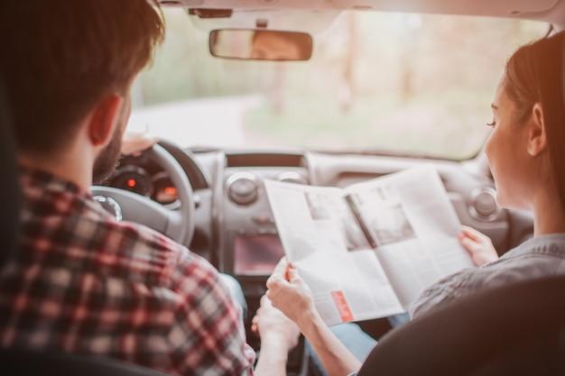 Junges paar reist. sie fahren im auto. mädchen hält karte und schaut sie an, während kerl fährt. sie folgen der straße.