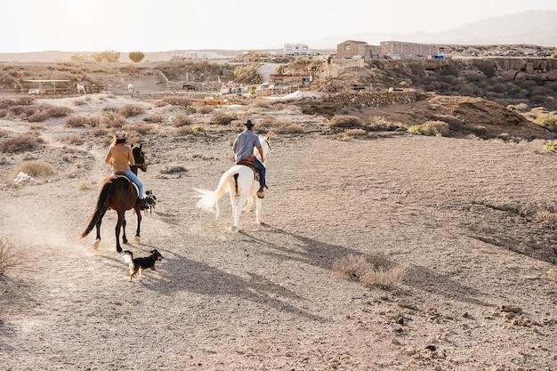 Junges paar reitet pferde, die bei sonnenuntergang einen ausflug mit hunden machen - hauptaugenmerk auf dem rücken der frau