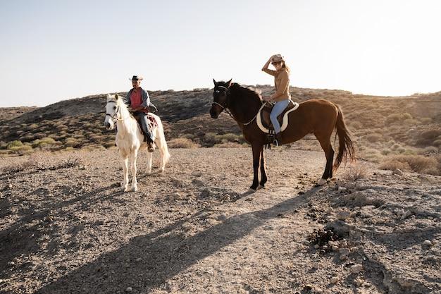 Junges paar reitet pferde, die während des sonnenuntergangs ausflüge auf die landschaft machen - hauptaugenmerk auf das gesicht der frau