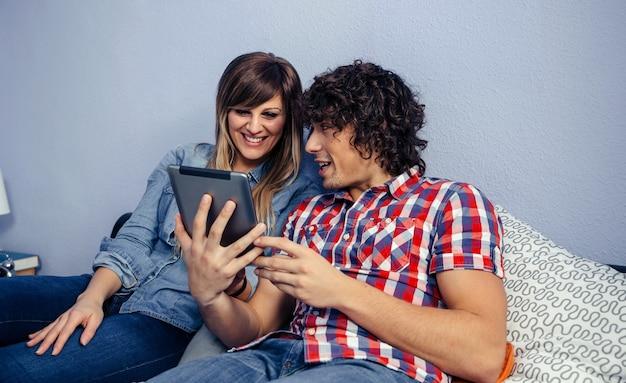 Junges paar schaut auf die tablette, die auf dem bett sitzt
