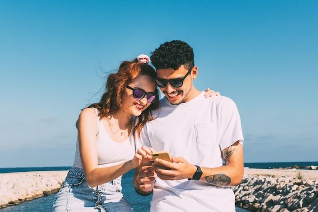 Junges paar schaut auf ihr smartphone vor dem strand