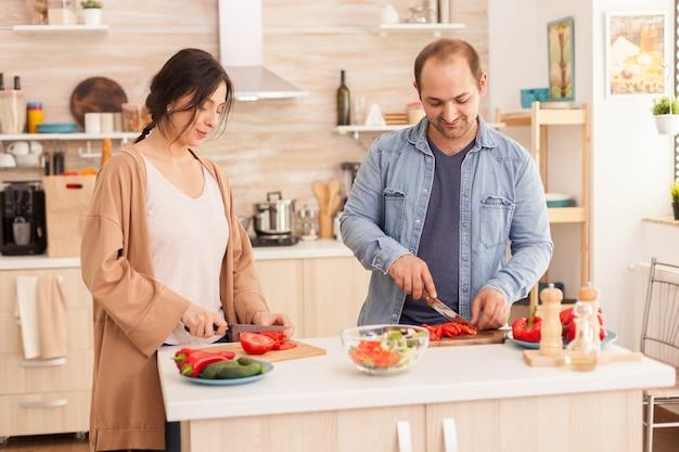 Junges paar schneidet tomaten für salat in der küche mit schneidebrett. glücklich verliebtes fröhliches und sorgloses paar, das sich gegenseitig hilft, das essen zuzubereiten