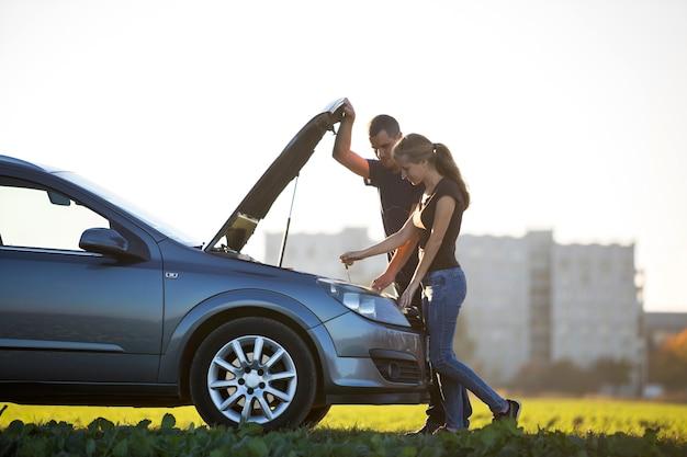 Junges paar, schöner mann und attraktive frau am auto mit geknallter motorhaube, die ölstand im motor unter verwendung des ölmessstabes auf klarem himmel prüft. transport, fahrzeugprobleme und pannenkonzept.