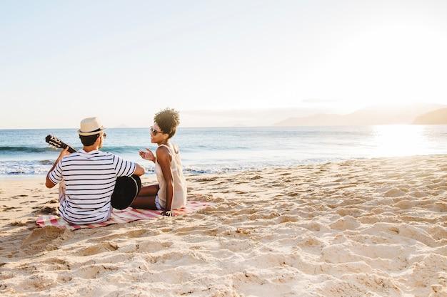 Junges paar sitzt am strand und spielt die gitarre