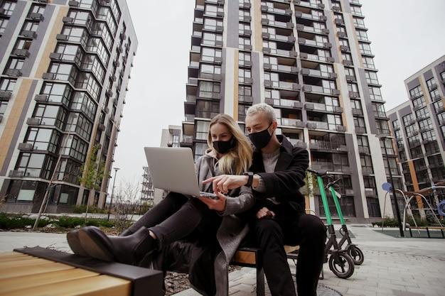 Junges paar sitzt auf bank im park nahe ihrer wohnung. sie tragen schwarze medizinische gesichtsmasken und halten abstand zu anderen menschen. pass auf dich auf! frau und mann, die film im park auf laptop schauen.