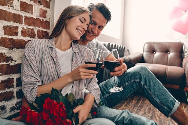 Junges paar sitzt auf dem boden mit gläsern wein und roten rosen. valentinstag. jubiläum. geburtstag.