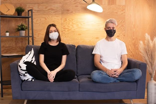 Junges paar sitzt auf der couch in masken und schaut in die kamera