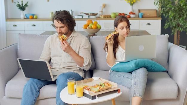 Junges paar sitzt auf der couch zusammen, isst eine pizza und arbeitet mit einem laptop in der nähe eines ...