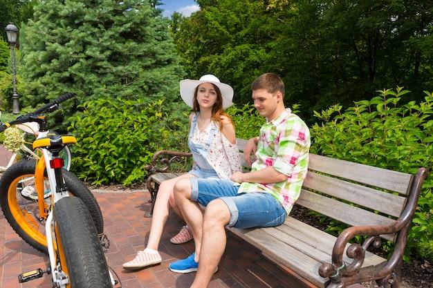 Junges paar sitzt auf einer bank in der nähe von fahrrädern, die auf einem gemauerten bürgersteig in einem schönen grünen park geparkt sind