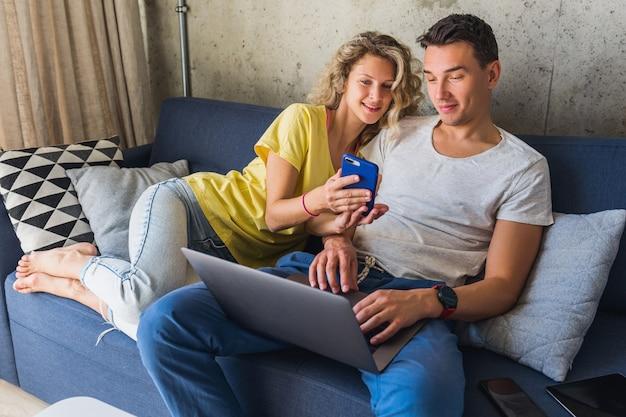 Junges paar sitzt auf sofa zu hause und schaut in laptop