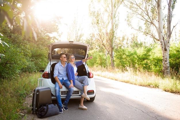Junges paar sitzt im kofferraum eines autos und wählt, wohin man reist