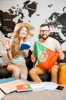 Junges paar sitzt mit portugiesischer flagge und reisepass im reisebüro auf dem weltkartenhintergrund und bereitet sich auf eine reise nach portugal vor