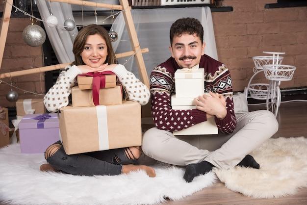 Junges paar sitzt mit weihnachtsgeschenken in der nähe von festlichen silbernen kugeln.