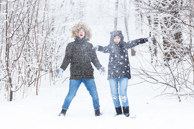 Junges paar spielt mit schnee im winterpark