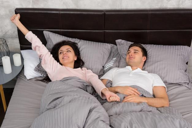 Junges paar streckt sich im bett und trägt pyjamas im schlafzimmer im loft-stil mit grauen farben