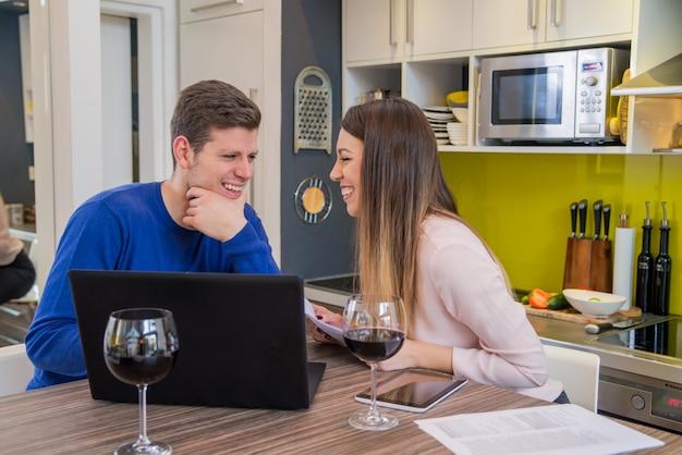 Junges paar sucht finanzielle dokumente in laptop am tisch im haus interieur. junge heimstudenten präsentieren e-learning-service