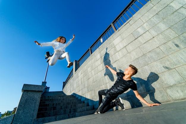 Junges paar tanzen auf der autobahn. fliegende haare. film. mann hält eine frau in einem tanz. erbsengefühle. tanz der leidenschaft.