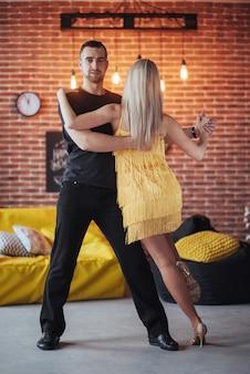 Junges paar tanzt lateinamerikanische musik: bachata, merengue, salsa. haltung mit zwei eleganzen auf café mit backsteinmauern