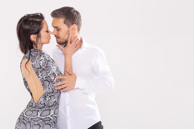 Junges paar tanzt latin dance bachata, merengue, salsa, kizomba. zwei eleganz posieren über weißer wand mit kopierraum