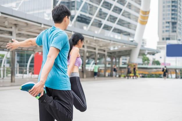 Junges paar trägt sportkleidung mit dehnübungen in der stadt