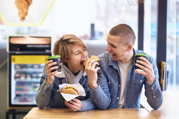 Junges paar traf sich im fast food, um burger zu essen