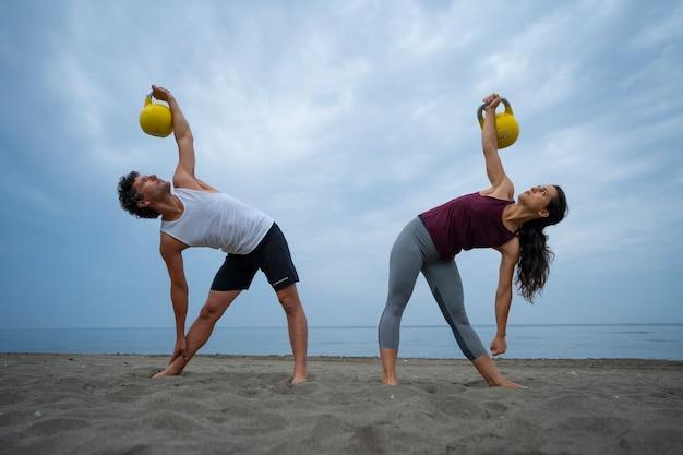 Junges paar trainiert am strand mit kesselglocken