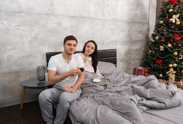 Junges paar trinkt kaffee in einem bett, trägt pyjamas, im schlafzimmer mit weihnachtsbaum und geschenken
