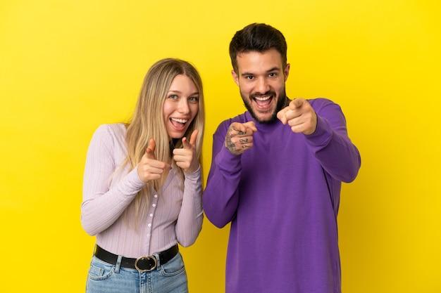 Junges paar über isoliertem gelbem hintergrund zeigt mit dem finger auf dich