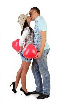 Junges paar umarmt, küsst und hält luftballons - herzisolat