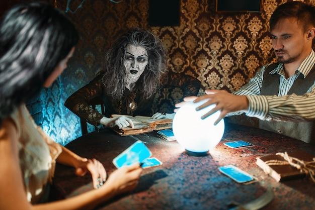 Junges paar und wahrsagerin am tisch mit kristallkugel auf spiritueller seance, gruseliger zauberer liest den zauber. weiblicher vorläufer ruft die geister